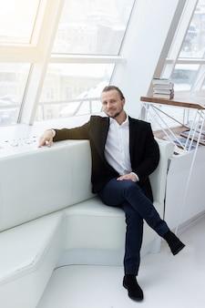 Портрет улыбающегося человека, сидящего на диване в белом современном интерьере. глядя на камеру. - вертикальное изображение