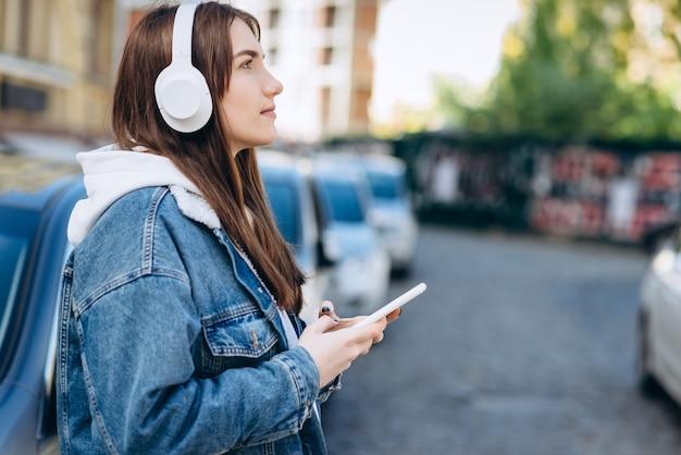 Девушка на городском фоне, в белых наушниках и смартфоне в руках, опираясь на машину