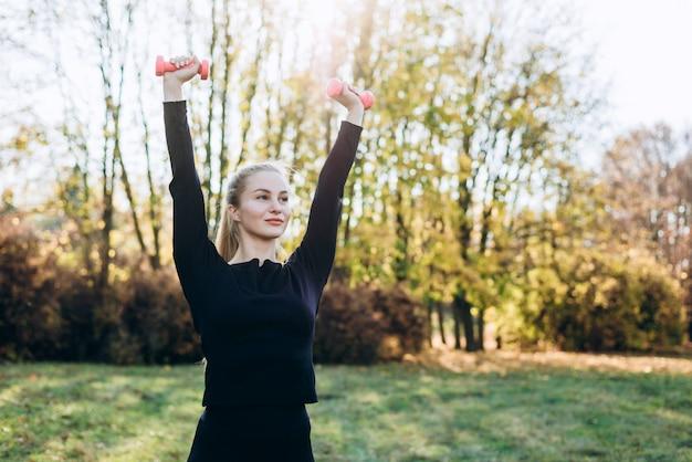 若い女性がアウトドアスポーツに行きます。ブロンドの女の子は、自然の公園でトレーニングです。