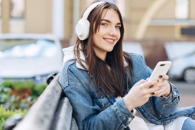 Улыбающаяся девушка сидит на скамейке и наслаждаясь, слушая музыку в белом, беспроводные наушники, держа смартфон в руке. улица с автомобилями на размытом фоне