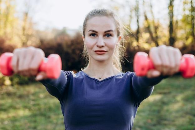 彼女のライフスタイルの一部として、ダンベルで運動を美しい若い女性。