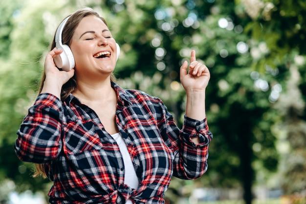 Стильно одетая, брюнетка большого размера в наушниках слушает любимую музыку, танцует на фоне города.