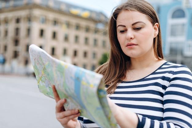 Молодая туристка стоит на площади, внимательно изучая туристическую карту