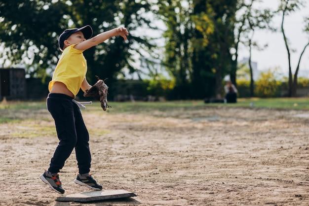 Маленький бейсболист бросает мяч