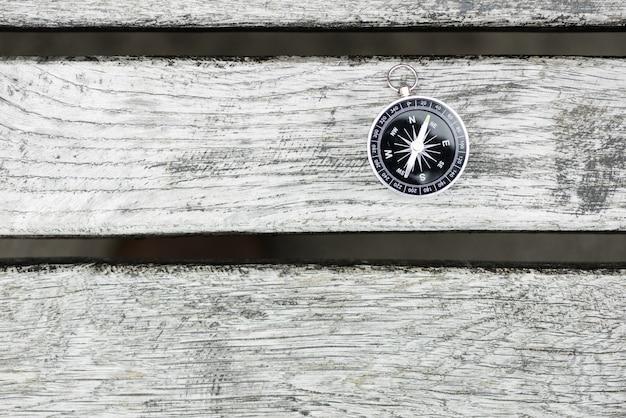 Компас на красивой деревянной поверхности. вид сверху