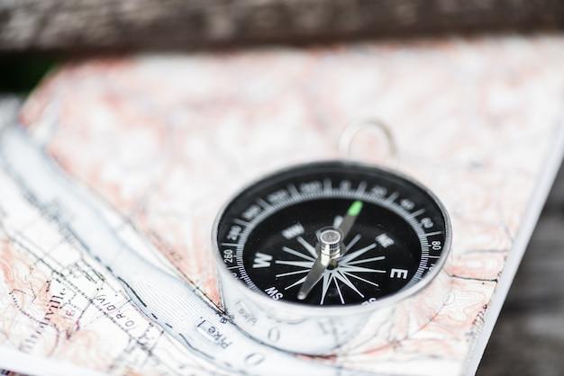 Компас и карта на красивой деревянной поверхности. вид сверху