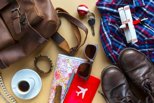 Плоский образ лежал коричневого кожаного аксессуара человека, чтобы спланировать путешествие в отпуск