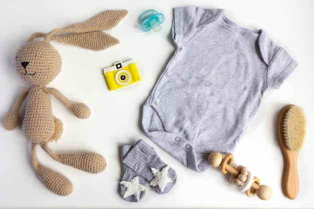 ユニセックスニュートラルなテーマのベビーシャワーまたは新生児保育園のコンセプトの服、おもちゃ、白い背景の上のアクセサリー。フラット横たわっていた、トップビュー。