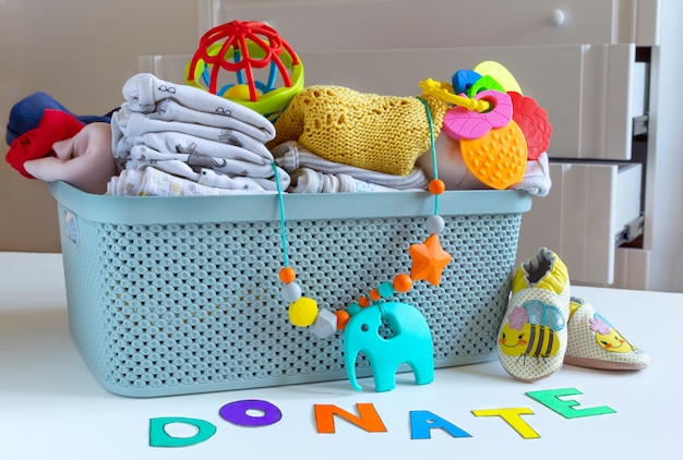 明るい背景に赤ちゃんユニセックス中立服と寄付アクセサリーの寄付ボックス