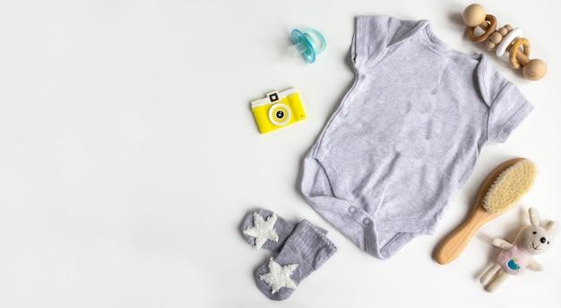 ユニセックス中立的な赤ちゃんの服、おもちゃ、白い背景の上のアクセサリー。フラット横たわっていた、トップビュー。コピースペース