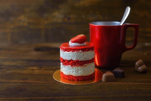 イチゴ、ビスケット、木製のテーブルにコーヒーの赤いカップケーキ