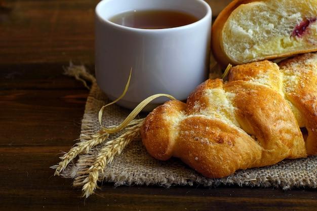 Выпечка со сливочным сыром и клубничным джемом и белой чашкой чая на темном деревянном
