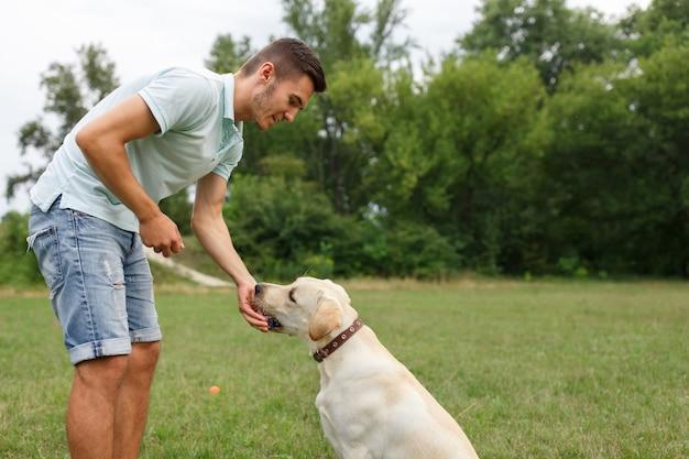 Счастливый молодой человек кормит собаку лабрадор на открытом воздухе