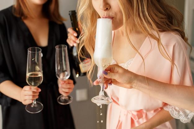 ヘンパーティーにガラスからシャンパンを飲む女性のクローズアップビュー