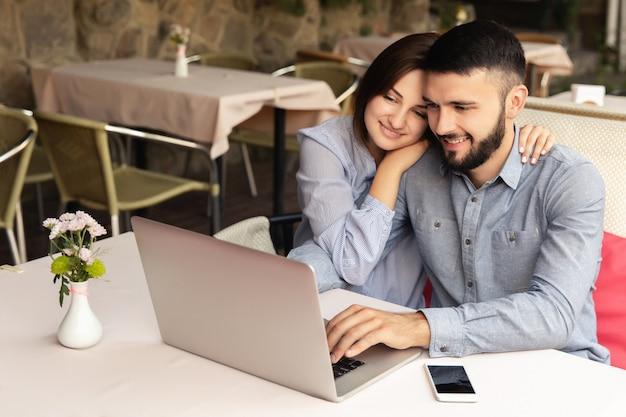 若いカップルが自宅で働いて、男と女が机に座って、屋内でラップトップに取り組んで