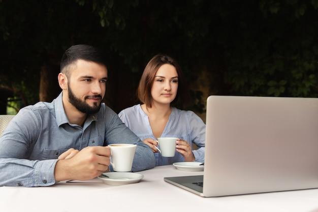 学生は自宅で勉強します。オンラインで勉強しています。屋内でラップトップを探している男女