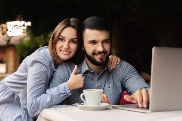 幸せな男と女の家で働いて、屋内でラップトップに取り組んでいる一杯のコーヒーと若いカップル