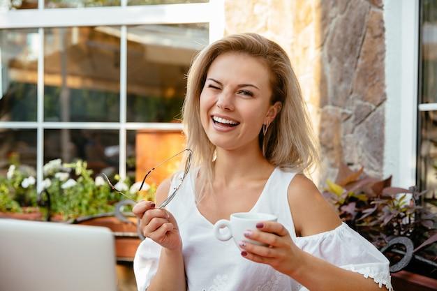Жизнерадостная женщина подмигивает, держа чашку кофе, отдыхая в кафе