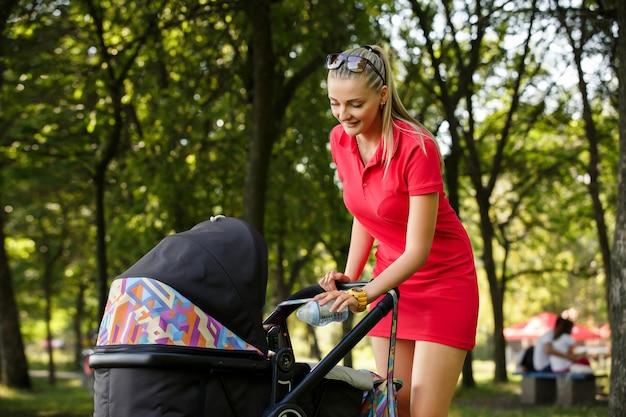 Молодая мама заглядывает в коляску и собиралась кормить ребенка бутылочкой детского питания