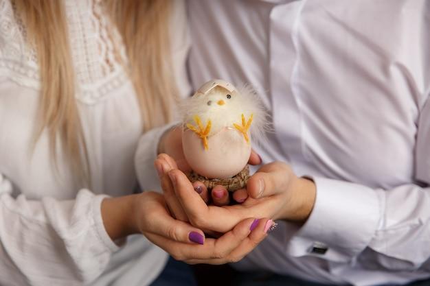 Пара держит в руках пасхальное яйцо с птенцом