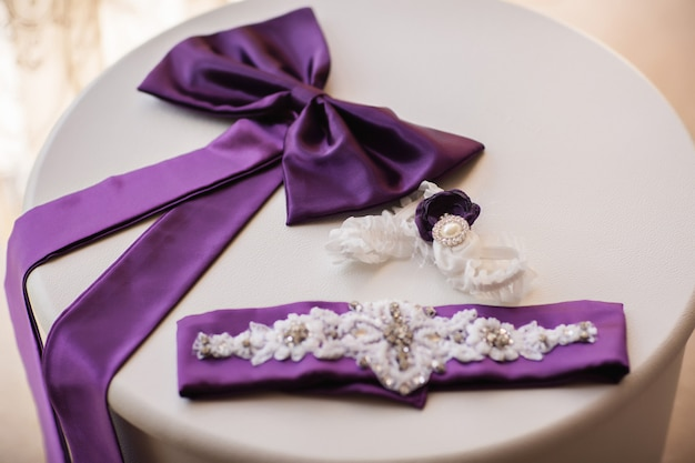 詳細と白いテーブルの上のウェディングドレスの要素。紫や紫の結婚式のコンセプトです。