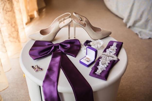 Свадебные аксессуары: туфли на высоком каблуке для невесты, элементы свадебного платья и обручальные кольца на кольцевой коробке на белом столе.