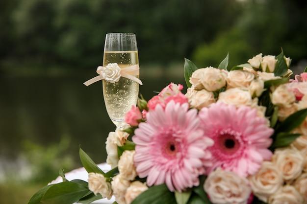 Свадебные цветы и бокал шампанского на столе. концепция свадебной церемонии