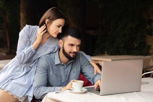 自宅でラップトップに取り組んでいる男女自宅で働く若いカップル