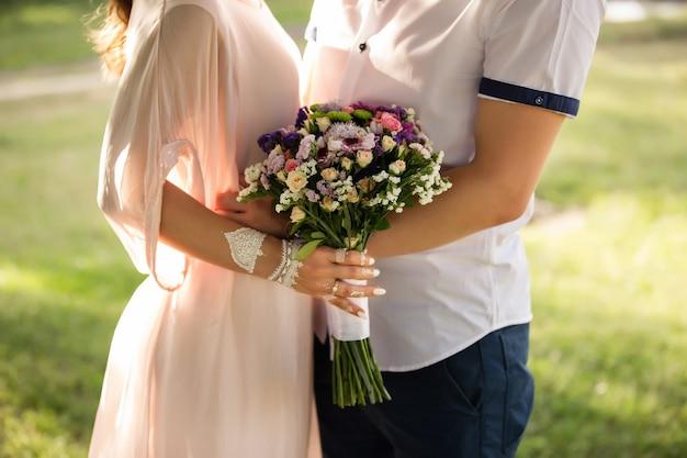 Летняя свадьба, пара держит букет цветов.