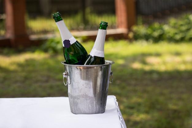 Бутылки шампанского в ведре со льдом