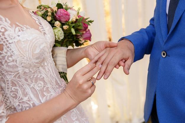 Свадебная церемония. невеста надевает обручальное кольцо на палец жениха