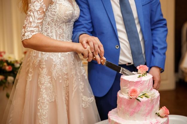 ピンクのウェディングケーキを切る新郎新婦