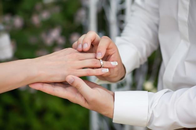 リング。結婚指輪。新しい幸せな家族の創造を象徴する、結婚指輪を交換する厳粛なプロセスでの新郎新婦の手。