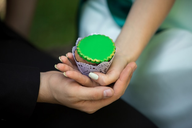 男と女の緑のカップケーキを保持しています。聖パトリックの日
