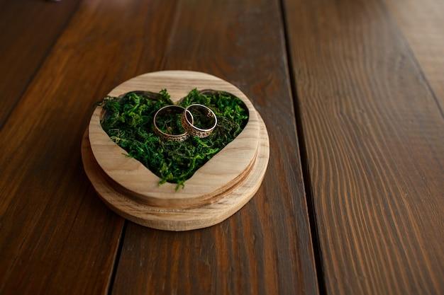 Деревенская свадьба. обручальные кольца в кольцевой коробке в форме сердца с зеленым мхом
