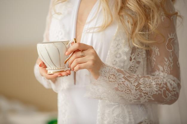 朝のコーヒー。一杯のコーヒーまたは紅茶、私室モデル、美しい花嫁の結婚式の朝を持つ女性