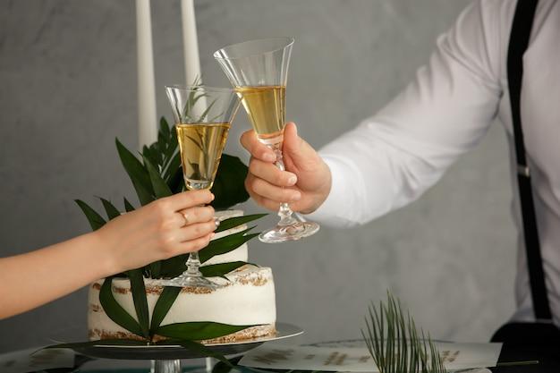 Романтический ужин или свидание с бокалами шампанского. тост и звон с алкогольными напитками. праздник на свадьбу. концепция брака