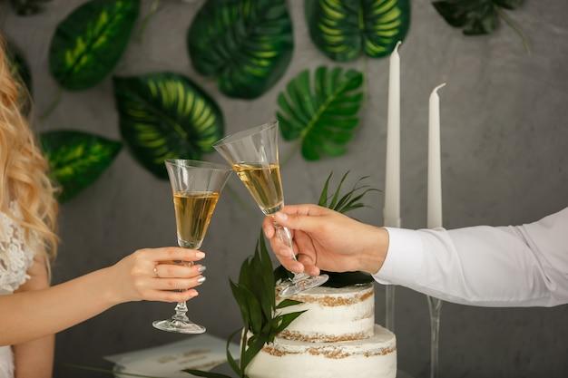 ロマンチックなディナーまたはシャンパングラスとのデート。トーストとアルコール飲料とチャリン。結婚パーティーのお祝い。結婚のコンセプト