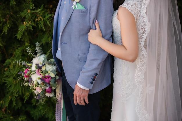 新婚カップル、手を繋いでいる新郎新婦。幸せな結婚式の日のコンセプト