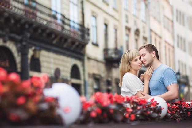 赤い花の近くの通りを受け入れる魅力的なカップル。