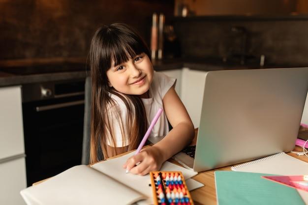 オンライン学習、自宅でオンラインレッスン中に宿題を勉強している女子高生