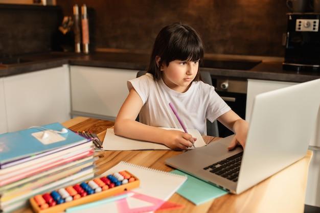 自宅学習。オンライン学習。ノートパソコンを持つ女子高生は家で宿題をします。ホームスクーリング。遠隔教育