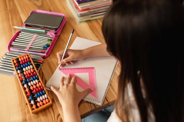 自宅でのオンライン学習。ラップトップを持つ女子高生は宿題をします。検疫中の遠隔教育
