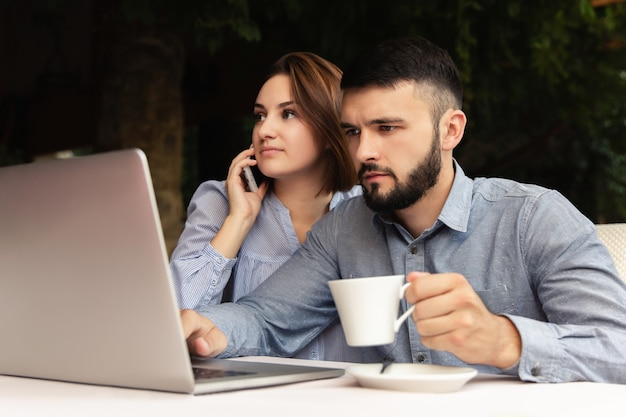 自宅で一杯のコーヒーを持つ男と机に座って、屋内でラップトップで作業するスマートフォンを持つ女性と自宅で働くカップル