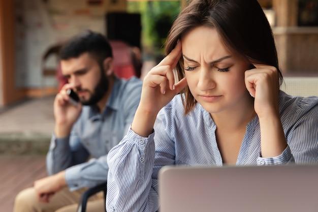 頭痛を持つ女性は彼女の頭を保持しています。壁にスマートフォンで話している男性