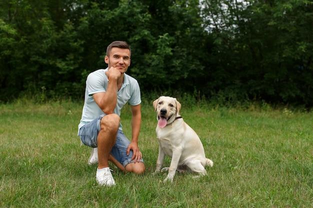 Молодой человек со счастливым лабрадором в парке