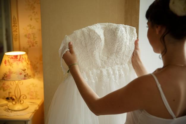 Невеста держит свадебное платье в теплой комнате