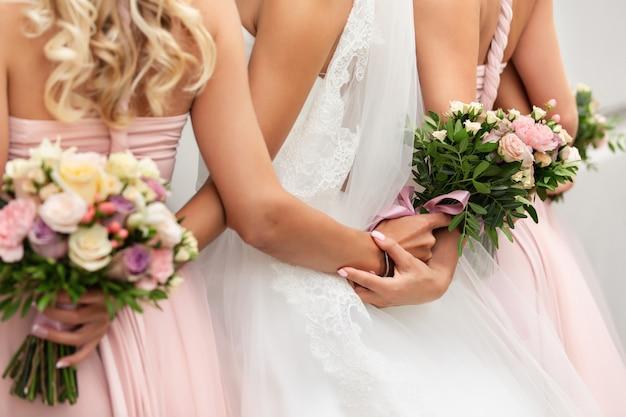 花嫁とブライドメイド、結婚式の日に花束を