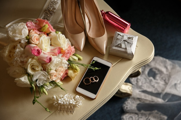 Обручальные кольца на смартфоне возле коробочки с кольцами, свадебные туфли на высоких каблуках, розовая флакончик для духов возле свадебного букета
