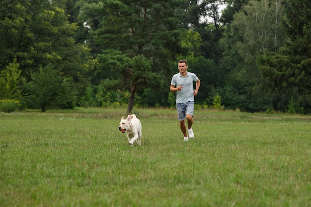 Счастливый молодой человек работает с собакой лабрадор на открытом воздухе